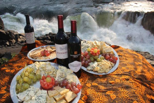 Image of wine and cheese board overlooking Moemba Falls, Zambezi River